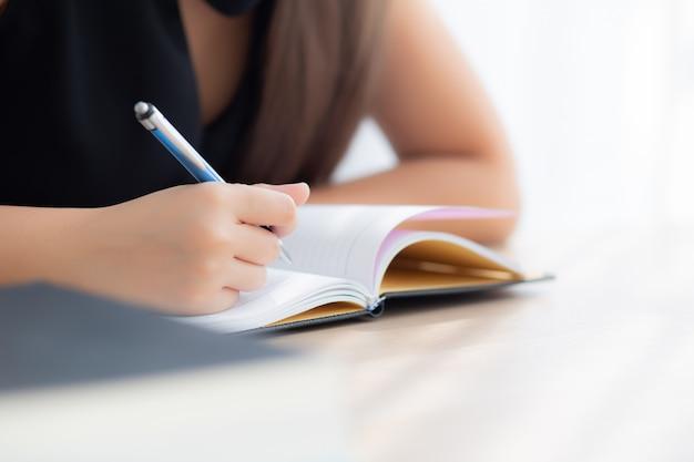 Mulher asiática do close up da mão que senta o estudo e que aprende o caderno da escrita