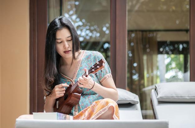 Mulher asiática do close up que joga o ukulele no sofá no terraço