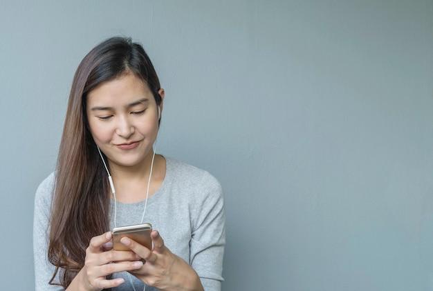 Mulher asiática do close up que senta-se para escuta a música da tabuleta com o fone de ouvido na emoção feliz