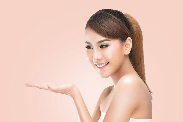 Mulher asiática do cuidado da beleza do cuidado do skincare que mostra o produto no lado com a mão aberta.