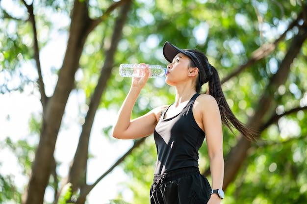 Mulher asiática do esporte bonito de meia-idade bebendo água após o conceito de corrida, saúde e esporte.
