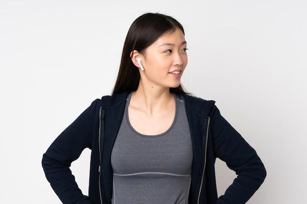 Mulher asiática do esporte jovem isolada na parede branca, posando com os braços no quadril e olhando de lado