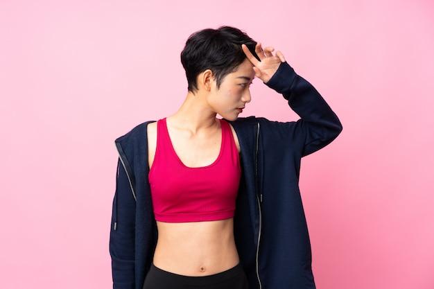 Mulher asiática do esporte jovem sobre parede rosa isolada com expressão cansada
