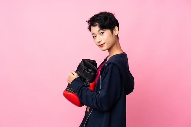 Mulher asiática do esporte jovem sobre parede rosa isolada com luvas de boxe