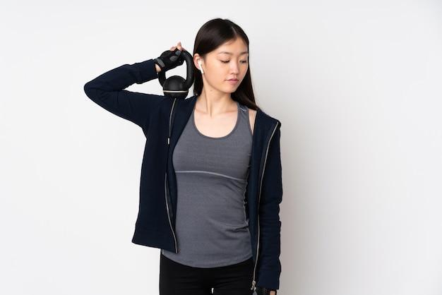 Mulher asiática do esporte novo na parede branca que faz o levantamento de peso com kettlebell