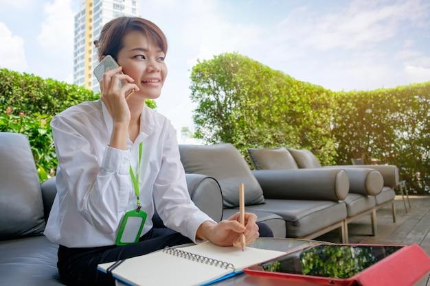 Mulher asiática do negócio bem sucedido que fala em seu telefone celular quando assentado fora na cidade.