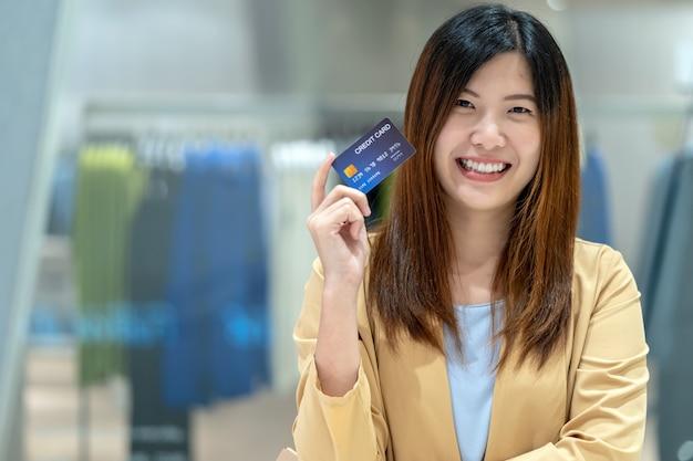 Mulher asiática do retrato segurando e apresentando o cartão de crédito para compras on-line
