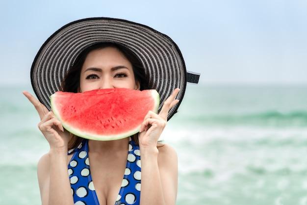 Mulher asiática do tempo feliz no terno de natação que guarda a fatia de melancia tropical na praia, conceito traval das férias de verão.