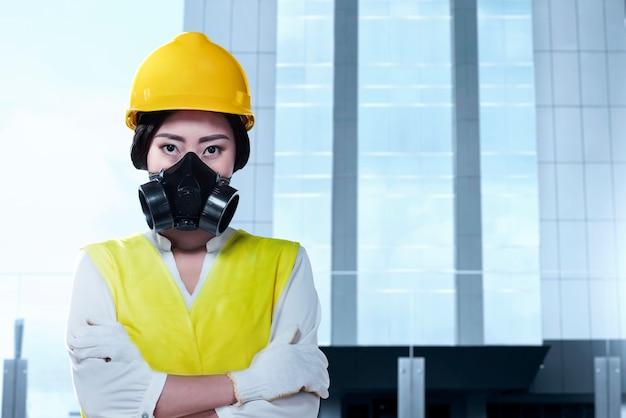 Mulher asiática do trabalhador com uma máscara protetora e pé de capacete amarelo