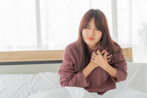 Mulher asiática doença cardíaca na cama