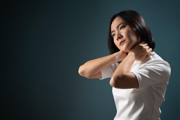 Mulher asiática doente com síndrome de dor no corpo e isolada sobre o azul