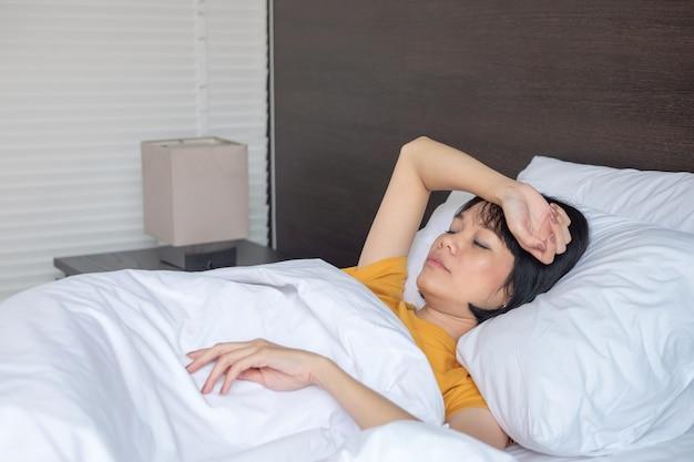 Mulher asiática doente e dormindo na cama branca do quarto