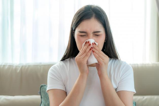 Mulher asiática doente e triste com espirros no nariz e tosse fria no lenço de papel porque a gripe e as bactérias fracas ou virais do tempo com poeira ou fumaça para uso médico.