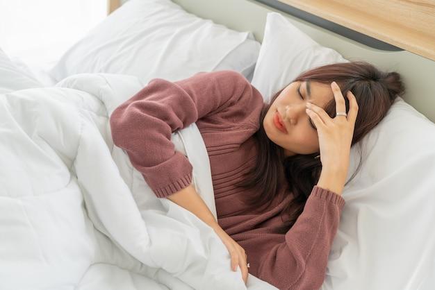 Mulher asiática dor de cabeça dormindo na cama