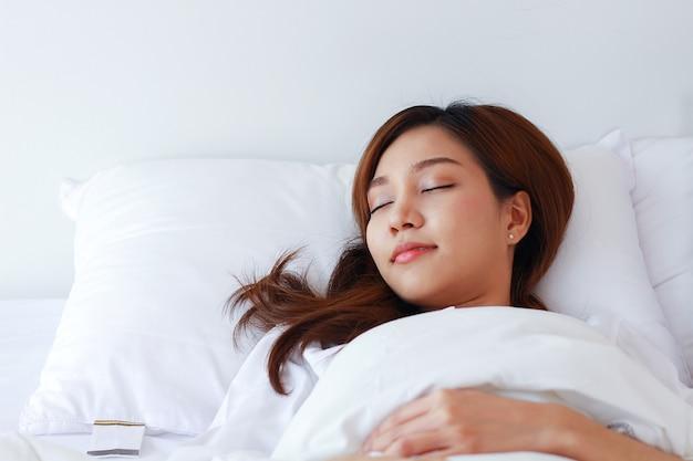 Mulher asiática dorme em uma cama branca de férias em casa.