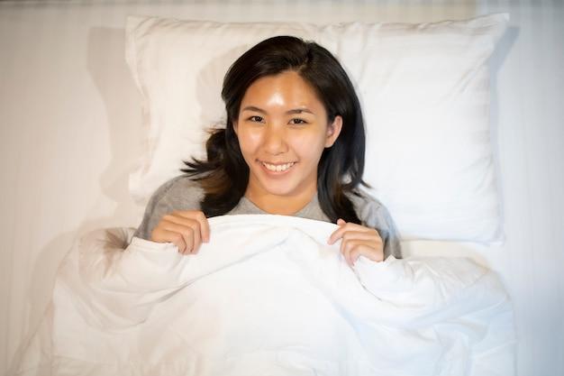 Mulher asiática dormindo em um colchão branco.