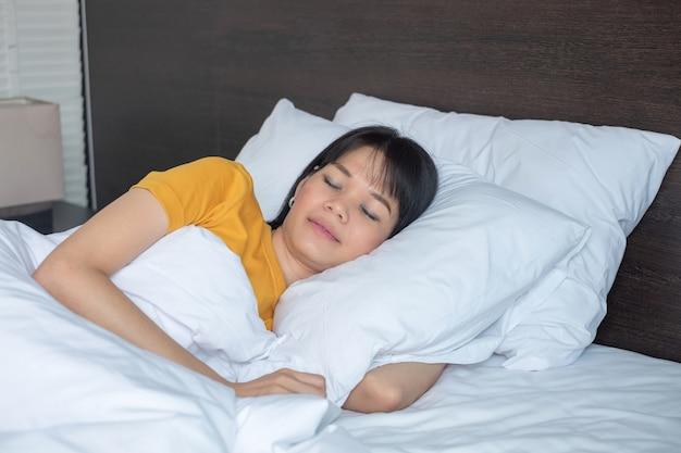Mulher asiática dormindo na cama branca do quarto
