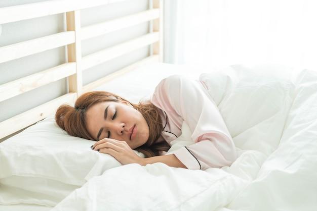 Mulher asiática dormindo na cama