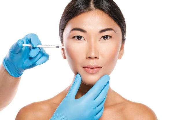 Mulher asiática durante a modulação da maçã do rosto ou procedimento de injeção de preenchimento isolado na parede branca