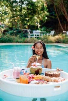 Mulher asiática e comida asiática. jovem mulher com cabelos escuros posa na piscina com mesa flutuante e um copo de suco.