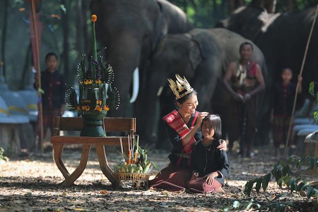 Mulher asiática e garota em traje tradicional nativo, sentado pelo conjunto de cerimônia de colheita