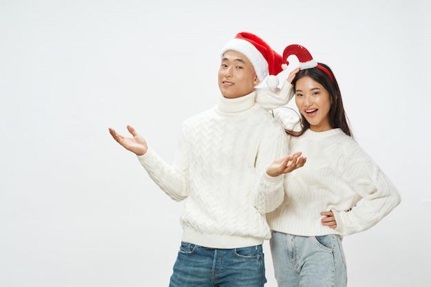 Mulher asiática e homem com chapéus de papai noel