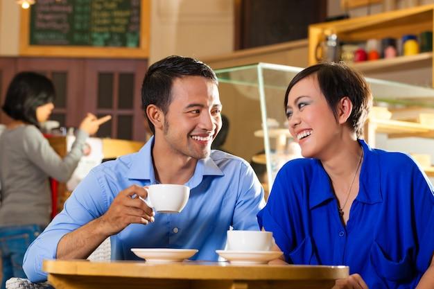 Mulher asiática e homem em uma cafeteria