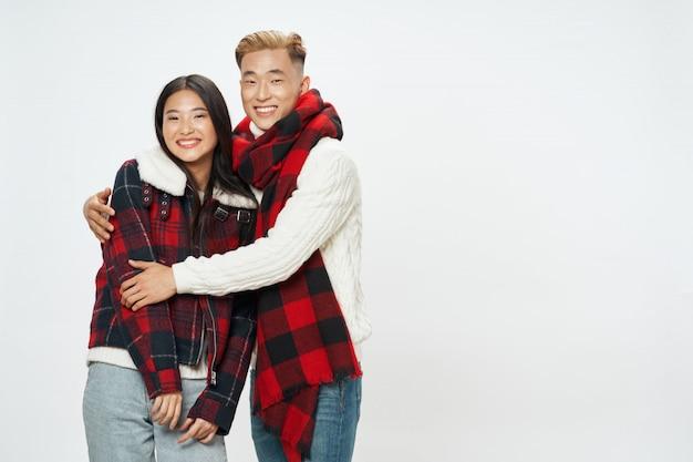 Mulher asiática e homem na parede posando juntos