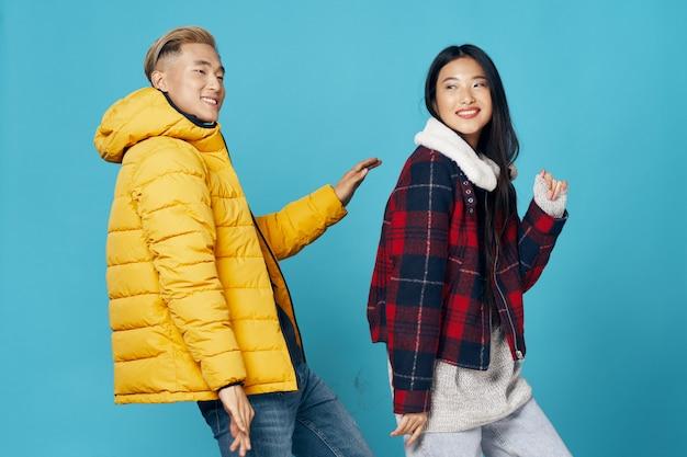 Mulher asiática e homem na superfície de cor brilhante, posando de modelo juntos