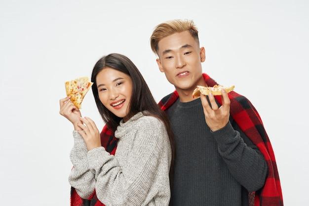 Mulher asiática e homem no espaço de cores brilhantes, posando juntos de modelo