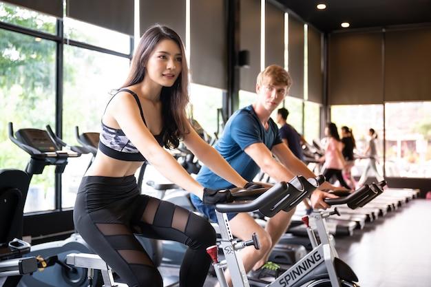 Mulher asiática e homem treino no ginásio de esporte, andar de bicicleta bicicleta para cardio