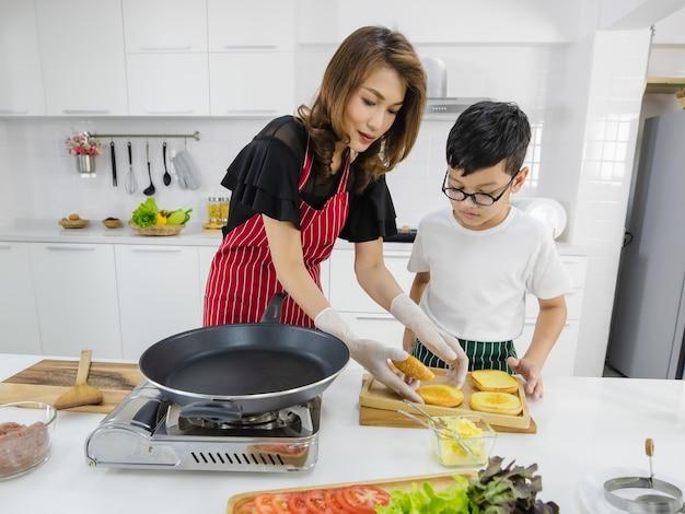 Mulher asiática e menino colocando pães frescos na panela quente enquanto cozinha hambúrgueres para o almoço na cozinha em casa. conceito de amor e tempo de relacionamento na família moderna.