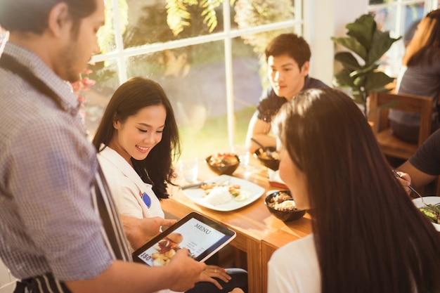 Mulher asiática e seus amigos estavam pedindo no menu, o garçom no restaurante pela manhã.