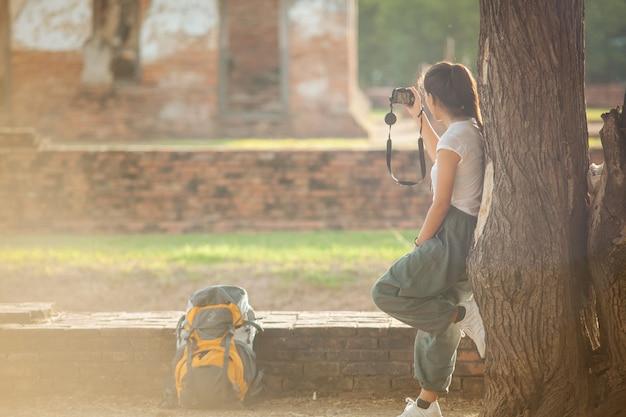Mulher asiática é tomar a foto do antigo templo em história de ayutthaya viagem do parque nacional em férias