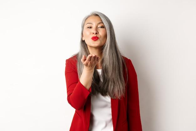 Mulher asiática elegante com blazer vermelho e lábios, soprando beijo no ar para a câmera, conceito de dia dos namorados e romance, fundo branco.