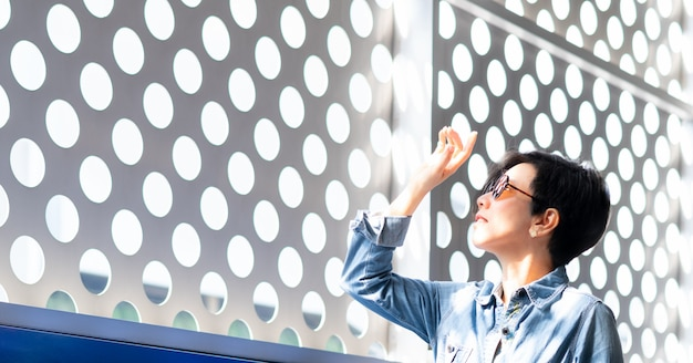 Mulher asiática elegante e de meia-idade, usando óculos de sol 100% de proteção contra luz uv, fique de pé e levante a mão para bloquear o brilho intenso e a luz do sol de fora para evitar a superexposição dos raios ultravioletas