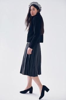 Mulher asiática elegante na boina e saia preta elegante