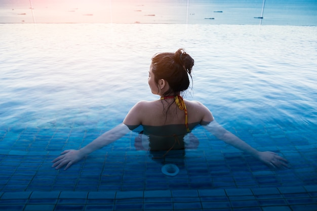 Mulher asiática em biquíni relaxante na piscina verão comcept