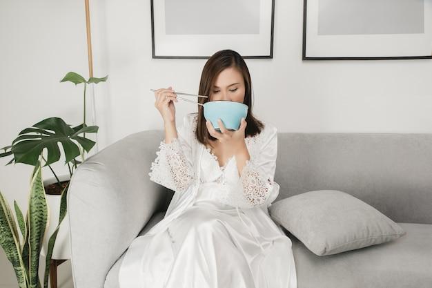 Mulher asiática em camisola de cetim branco sentada em um sofá cinza e comendo comida