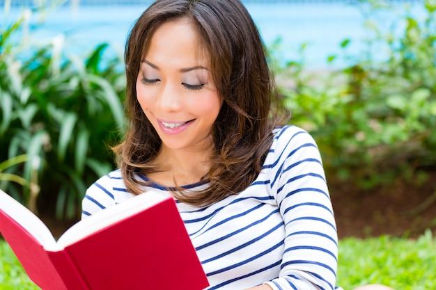 Mulher asiática em casa no livro de leitura do jardim
