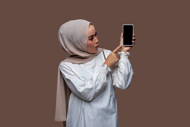 Mulher asiática em hijab chocada ao apontar para a tela do telefone
