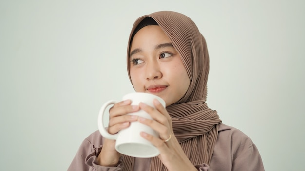 Mulher asiática em hijab pensando em inspiração enquanto saboreia uma bebida em casa