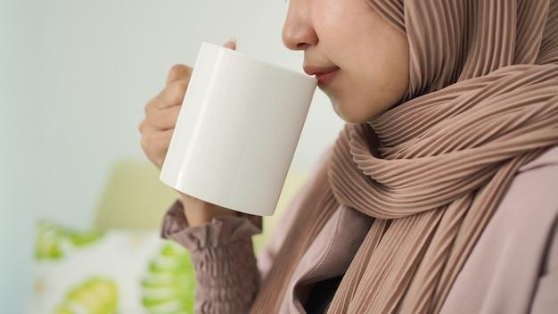 Mulher asiática em hijab tomando uma bebida em casa