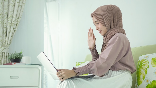 Mulher asiática em hijab trabalhando em casa cumprimentando alguém na tela do laptop