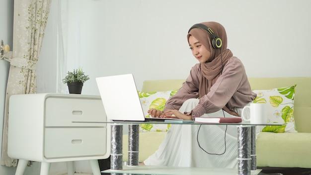 Mulher asiática em hijab trabalhando em casa digitando no laptop enquanto ouve