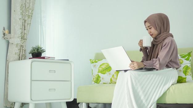 Mulher asiática em hijab trabalhando em casa sentada relaxada tomando uma bebida