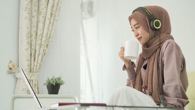 Mulher asiática em hijab trabalhando em casa tomando um drinque enquanto ouve