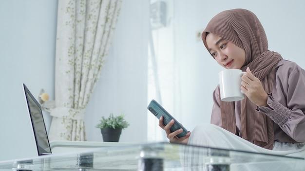 Mulher asiática em hijab trabalhando em casa tomando um drinque
