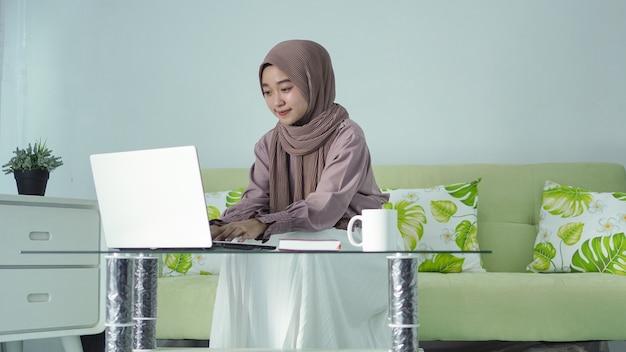 Mulher asiática em hijab trabalhando em casa usando seu laptop