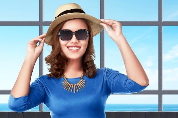 Mulher asiática em pé com chapéu e óculos de sol no resort com vista para o mar.